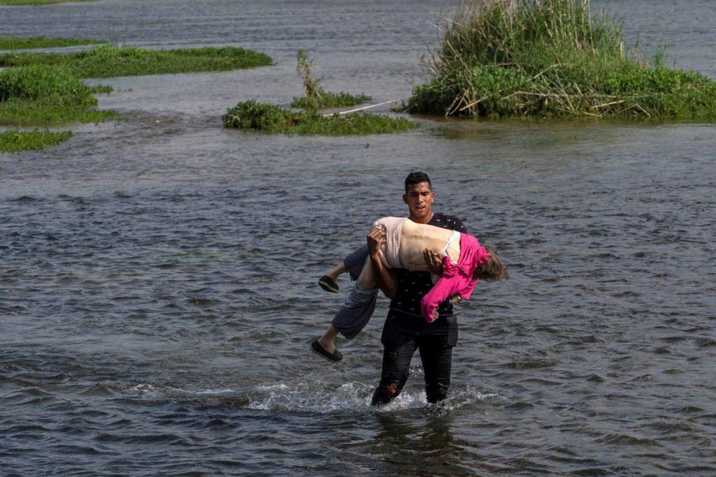 Anciano venezolano cruzando el río Bravo en brazos de otro migrante, imagen de dos crisis sin fin
